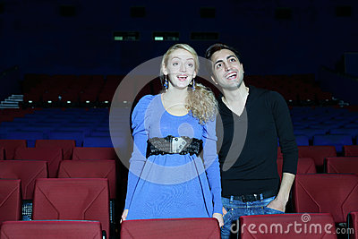 Young man and woman stand, watch movie and laugh