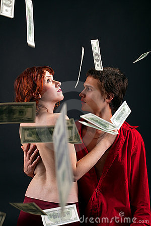 Young man and woman under money fall