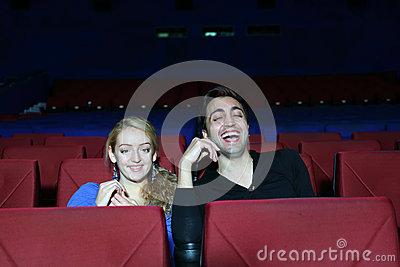 Young man and woman watch movie and laugh in movie theater