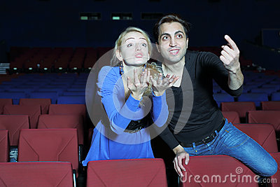 Young man and woman watch movie and root for movie characters