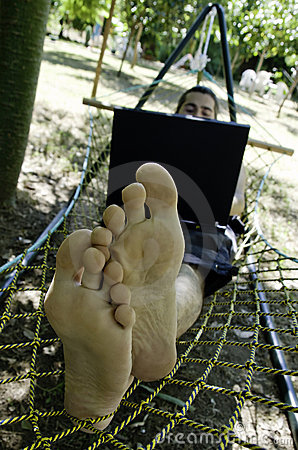 Young man working on his laptop in hammock