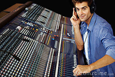 Young man working on sound mixer console
