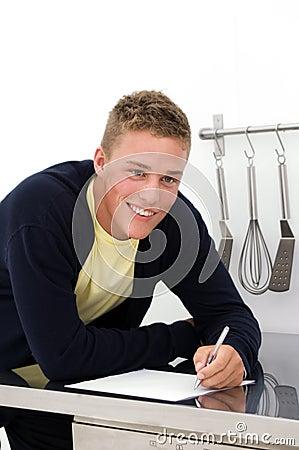 Young man writing down recipe