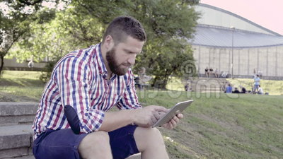 Young man writing message on tablet, sitting on stairs. Slider shot. stock video
