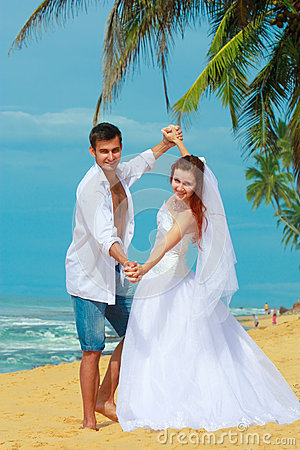Young married couple dancing on a beach in a tropical destination