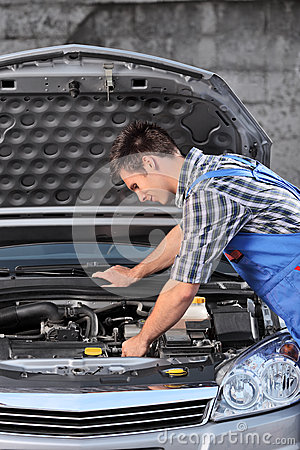 Young mechanic in overalls examining an automobile