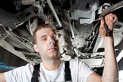 Young Mechanic working below car in garage