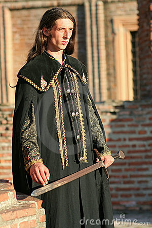 Young medieval prince with saber and black mantle