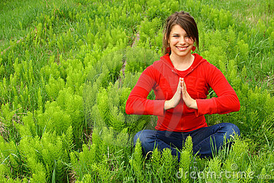 Young meditating in a field