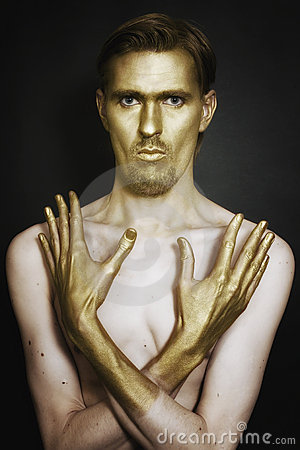 Young men with gold makeup on face and han