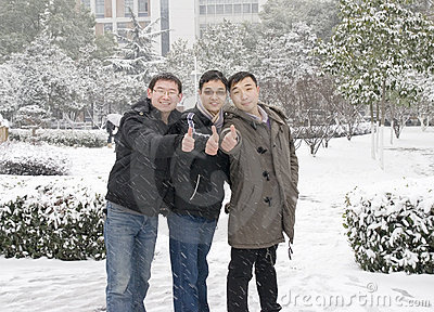 Young men thumbs up in snow
