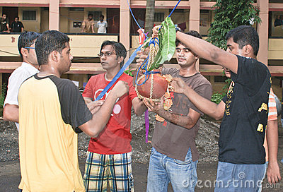 Young men tying a pot of butter during Janmasthami Editorial Image