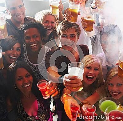 Young men and women raising drinks