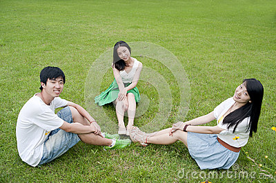 The young men and women sitting on the grass