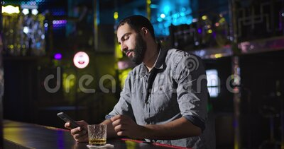 Young Middle Eastern man using smartphone and drinking alcohol next to bar counter in night club. Bored handsome guy. Resting alone. Cinema 4k ProRes HQ stock video