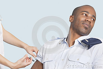 Young military man looking away as being injected by nurse over light blue background