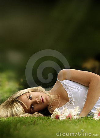 Young model laying down in grass