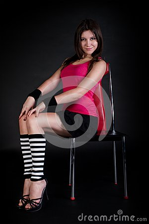 Young model sits on a red chair