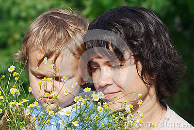 Young mom with her son among the summer daisies