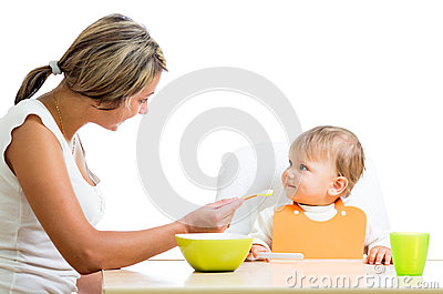 Young mom spoon feeding her cute baby girl