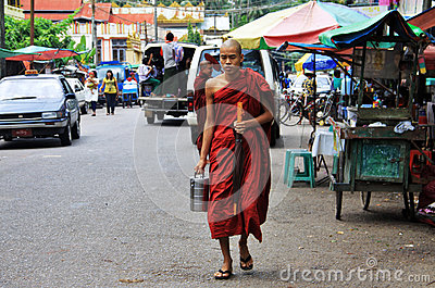 Young monk walking in Yangon with offering lunch Editorial Photo