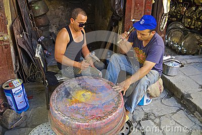 Young moroccan men forging a copper pot Editorial Photography