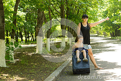 Young mother asking for a lift by the roadside