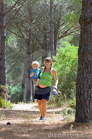 Young mother carrying her son and walking through woods