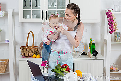 Young mother feeds child in the kitchen.