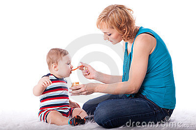 Young mother feeds  her baby.