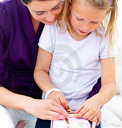 Young mother with her daughter opening gift