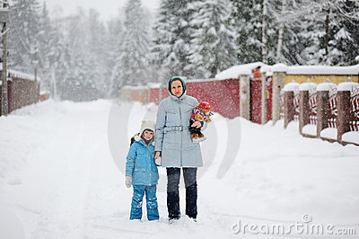 Young mother and her daughter in a snowfall