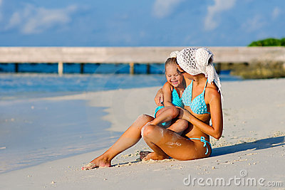 Young mother and her daughter on tropical beach