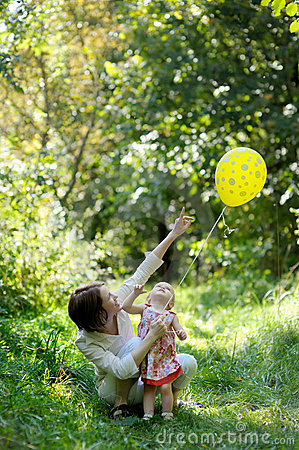 Young mother and her little baby with a balloon