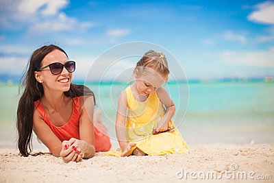 Young mother and her little daughter lying at
