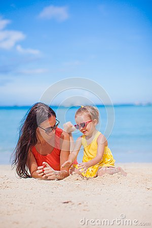 Young mother and her little daughter lying on