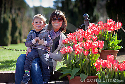 Young mother and her little son in a tulip garden