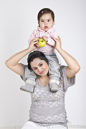 Young mother holding her toddler on shoulders