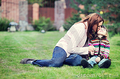 Young mother kisses her daughter on the lawn