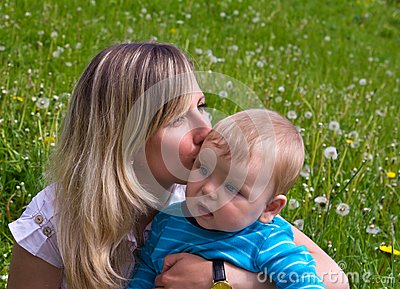 Young mother kisses her little son