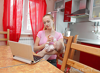 Young mother on kitchen with the laptop