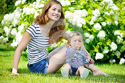 Young mother and little daughter on green grass