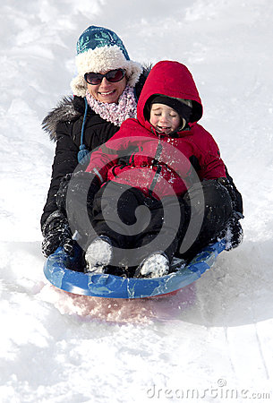 Young mother and son sledding down a snow hill
