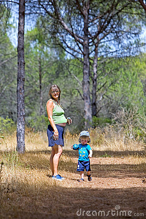 Young mother and son walking through woods