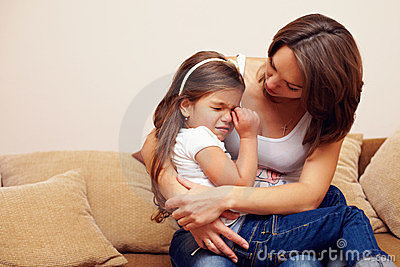 Young mother soothing and hugging crying baby girl
