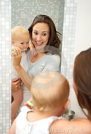 Young mother teaching cute baby how to brush teeth with toothbrush
