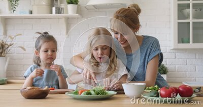 Young mother teaching kids daughters cutting vegetable salad in kitchen stock video