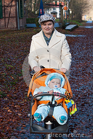 Young mother walking with baby boy in orange pram
