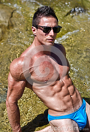Young muscle man outdoors in water showing muscular abs, pecs and arms