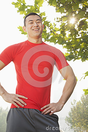Free Young Muscular Man In Red Shirt Standing And Smiling, Outdoors In A Park In Beijing Royalty Free Stock Image - 31106646